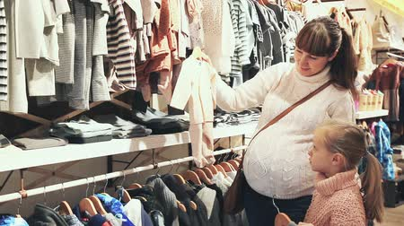 crawlers : pregnant mother and small daughter choosing clothes for baby in children cloths shop