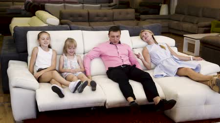 irmãs : Family of four are choosing a new sofa-transformer in furniture store.