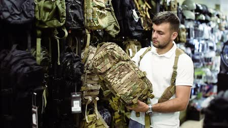 bulletproof : Young male customer choise camouflage bag in airsoft shop