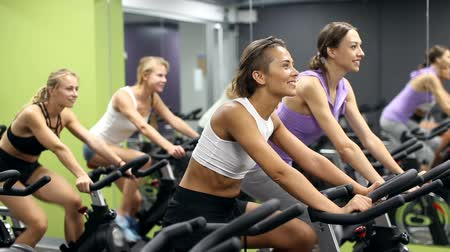 bisiklete binme : Sporty women on cardio training on exercycles in health club Stok Video