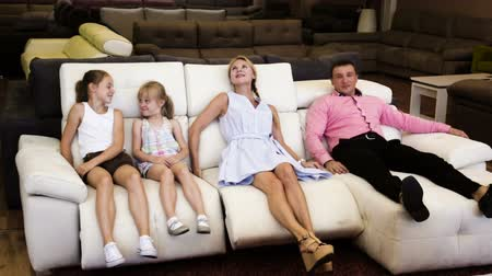 lojas : Man and woman with their children are choosing a new sofa-transformer in furniture store.