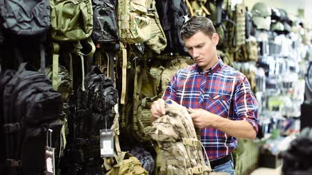 bulletproof : Man choosing textile backpack gun in military shop