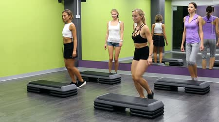 step : Group of sporty women working out with steppers in gym