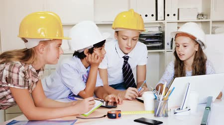 stavitel : Group of children in helmet talking about building near laptop