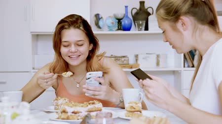 spoons : Girl is playfull talking by phone and her girlfriend is interesting it at home.