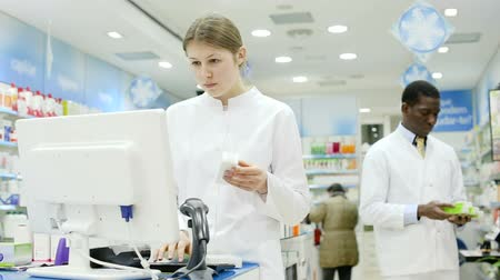 competence : Two professional pharmacists working behind the counter in modern pharmacy