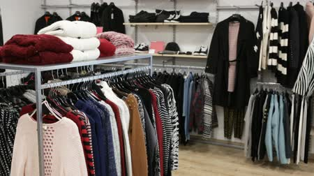 rendes : Ordinary apparel store with different clothes on hangers