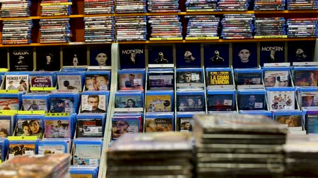compact disc : BARCELONA, SPAIN - FEBRUARY 15, 2018: Stacks of new DVDs with various films and serials in store