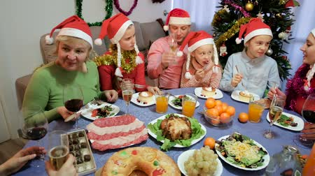 мишура : Happy family is talking at the table in time celebration New Year at home. Стоковые видеозаписи
