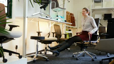retailer : Satisfied young woman sitting in the ergonomic office chair in the store before buying
