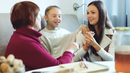 fondness : Grandmother with daughter and granddaughter enjoying conversation on sofa at home Stock Footage