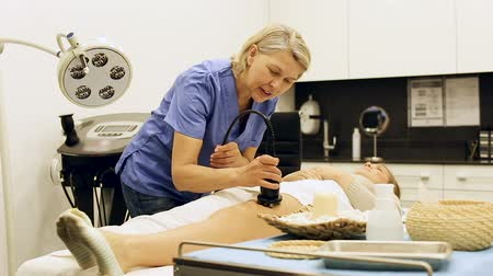cellulite treatment : Professional cosmetician performing body treatment in clinic of esthetic cosmetology