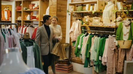 traje de passeio : Couple is satisfied shopping and walking with the package in the clothes store. Stock Footage