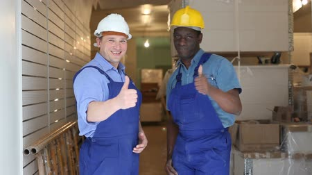 overhauls : Portrait of two confident professional construction workers standing at an indoors building site