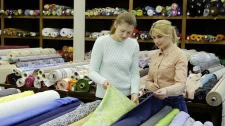 cortes : Polite female seller helping young woman in choice of interesting cloth in textile shop Stock Footage