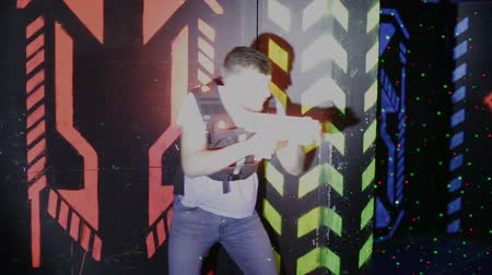 targeting : Modern young people with laser pistols playing laser tag on dark labyrinth