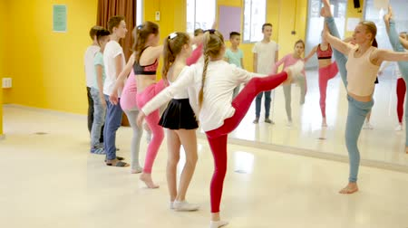 hall : Group of children participating in dance class, following their teacher in dance school Stock mozgókép
