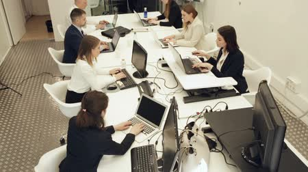 interior : Successful coworkers engaged in business activities in busy open plan office