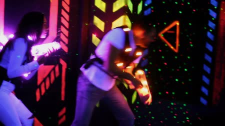 painless : Modern young people with laser pistols playing laser tag on dark labyrinth