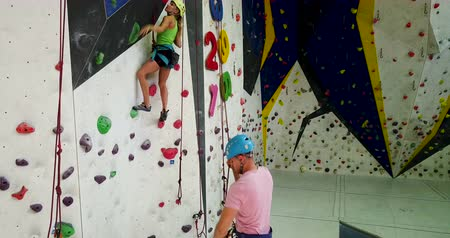 safeness : Sporty couple of climbers dressed in rock climbing outfit training at bouldering gym Stock Footage