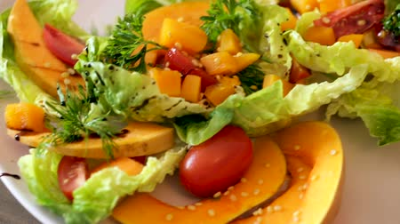 olive colored : Tasty salad of baked pumpkin, cherry tomatoes, sesame and sauce Stock Footage