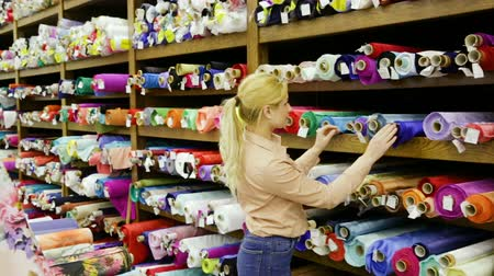 vystavený : Young woman looking for interesting cloth in textile shop
