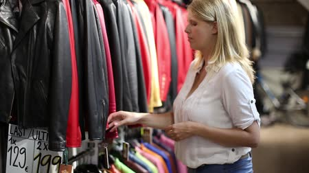 new clothes : Womens Fashion Choosing A Stylish Leather Jacket Stock Footage