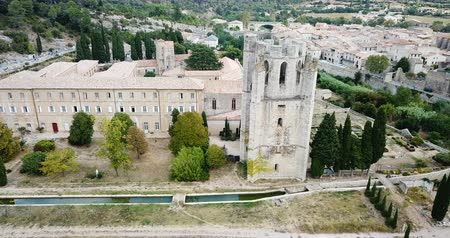 romanesk : Aerial view of the Romanesque Benedictine Abbey Sainte-Marie dOrbieu in commune of Lagrasse in southern France Stok Video