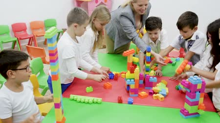 elsődleges : Building blocks from plastic toy blocks during lesson in classroom
