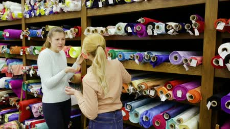 vystavený : Smiling young women shopping together in textile shop, choosing textiles for dressmaking