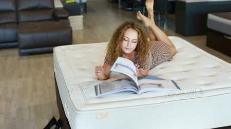 katalog : Portrait of attractive girl lying in bed, looking at catalog