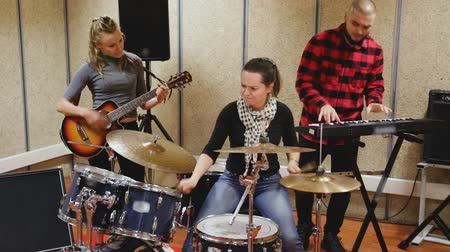 громкоговорители : Passionate emotional female drummer with her bandmates practicing in rehearsal room