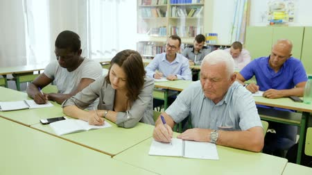 razem : Mature man and woman taking a written exam in the classroom Wideo