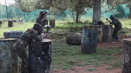 paintball : Paintball players in camouflages and masks aiming with guns in shootout outdoors Stock Footage