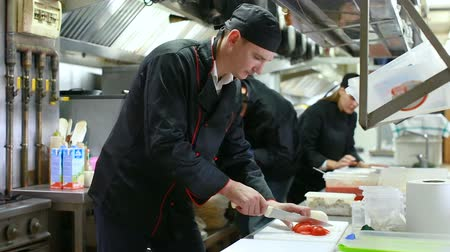 tray : Cheerful cooks dressed in black uniform at restaurant kitchen Stock Footage