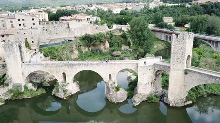 reddish : View from drone of medieval Spain town of Besalu with Romanesque bridge over Fluvia river