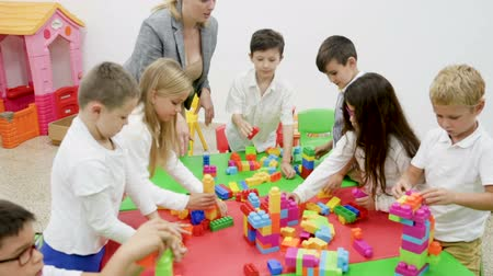 chlapík : Building blocks from plastic toy blocks during lesson in classroom