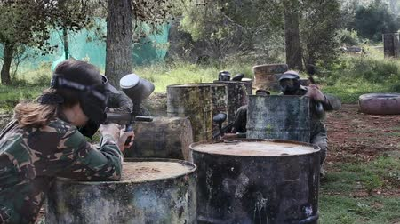 populární : Paintball players in camouflages and masks aiming with guns in shootout outdoors Dostupné videozáznamy