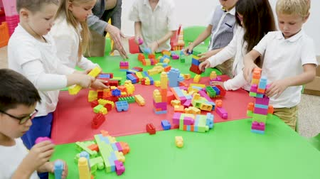 spolužák : Cute schoolchildren creating constructions from blocks with teacher in classroom