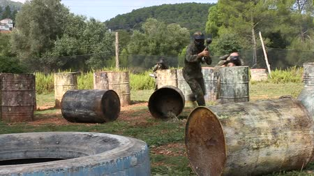 paintball : Paintball players aiming and shooting with guns at opposing team outdoors Stock Footage
