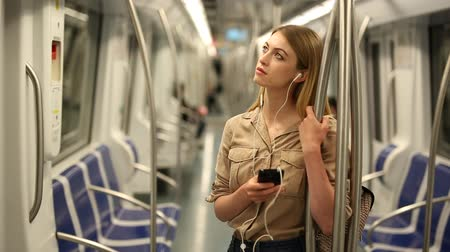 mozdony : Young woman with a smartphone and headphones