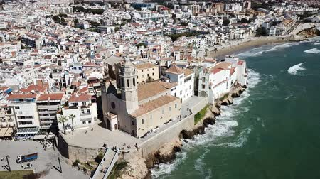 hegytömb : Aerial view of Sitges small town with church on Mediterranean coastline, Spain Stock mozgókép