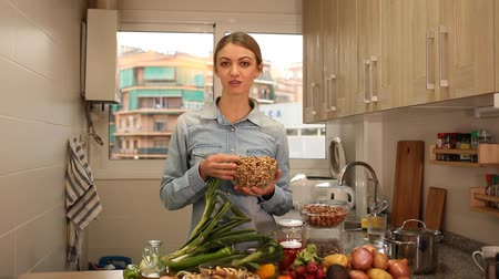 nozes : Attractive girl holding glass bowl with hazelnuts in her kitchen. Concept of healthy nutrition