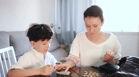 giveaway : Portrait of positive woman giving money to teen boy in home interior Stock Footage