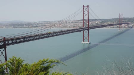 impressive skyline : Panoramic view of 25 de Abril Bridge - suspension bridge across Tagus river connecting Lisbon city to municipality of Almada, Portugal