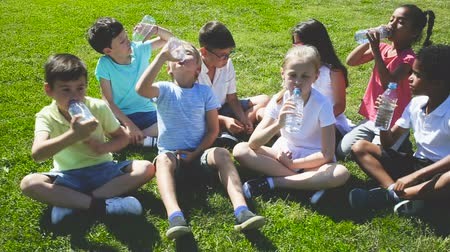 frasco pequeno : Group of children drink water from bottles on the summer lawn