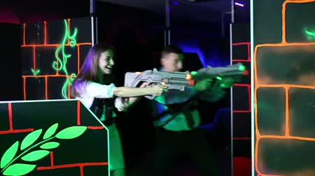 painless : Men and women in business suits playing laser tag emotionally in dark room