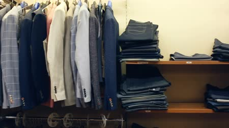 self promotion : Variety of different suit jackets exposed on clothing rack in men clothes shop