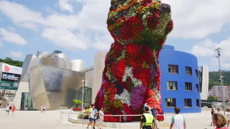 basque : BILBAO, SPAIN - JULY 16, 2019: Worlds largest flower sculpture of Puppy in front of Guggenheim Museum of modern and contemporary art