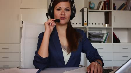 dispatcher : Office worker woman is working at a computer and talking by headset with client in the office Stock Footage